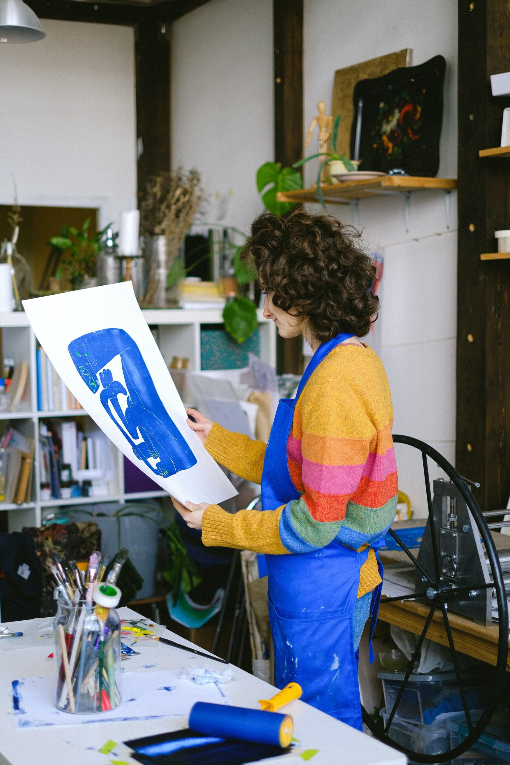 Selbstmotivation 3 Künstlerin betrachtet ihr fertig gemaltes Kunstwerk