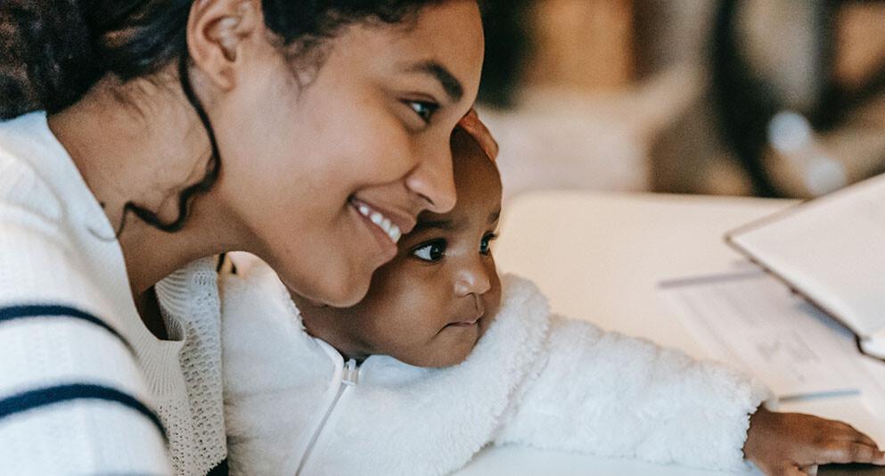 Junge Mama schaut sich etwas mit ihrem Baby auf dem Laptop an