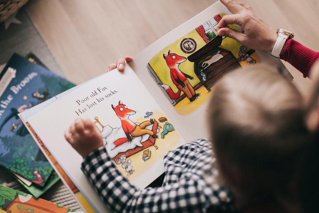 Familie liest Buch fuer fruehe Umweltbildung