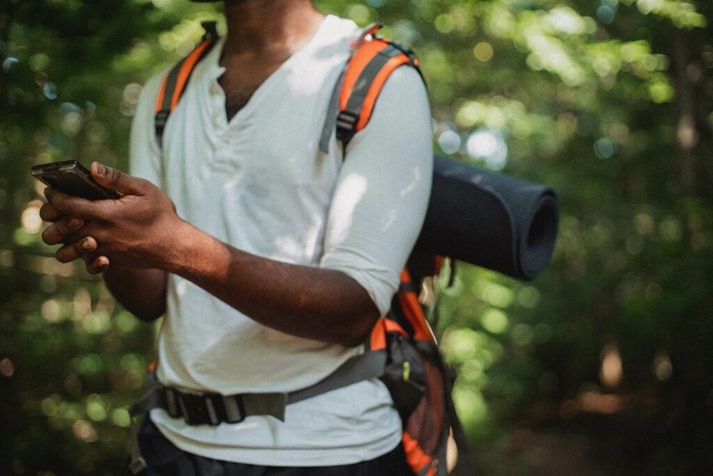 Mann mit Handy beim Geocaching