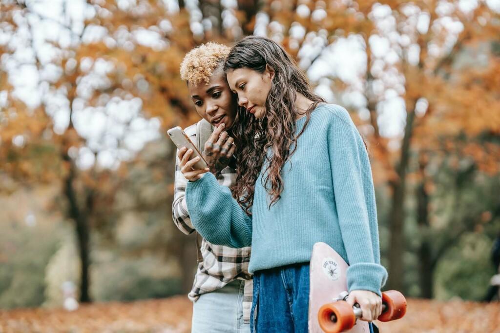 Zwei Maedchen suchen mit Handy nach Geocaching Schatz