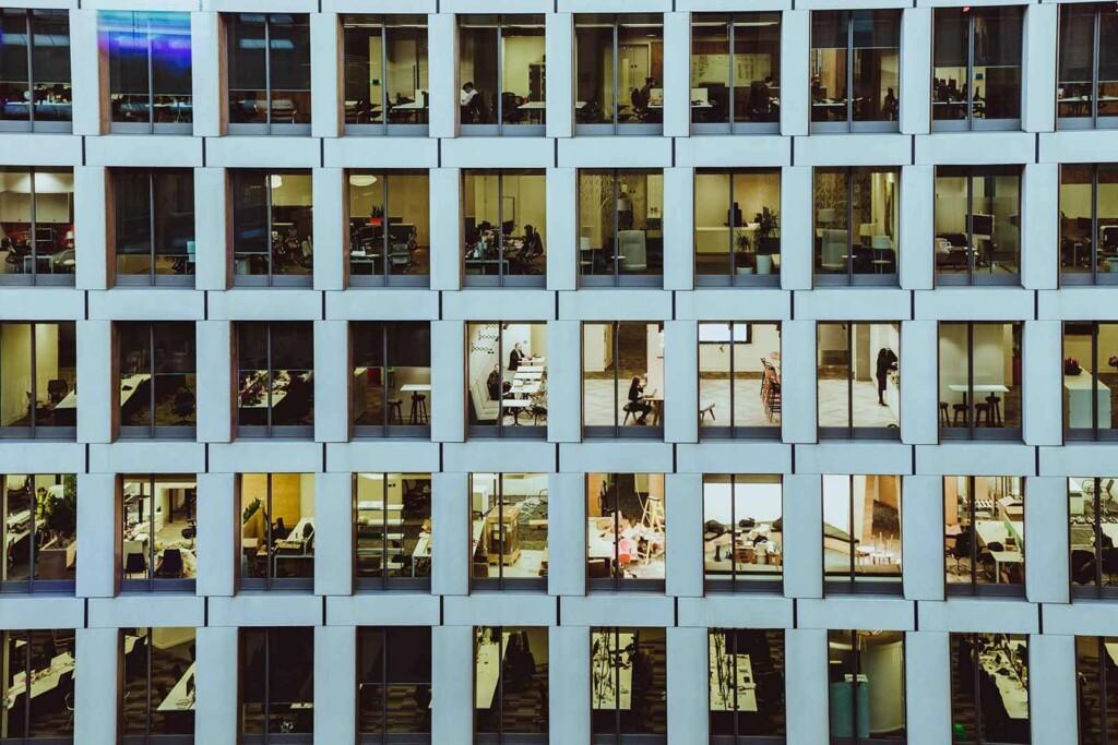 bürogebäude mit vielen büros in denen von 9 to 5 gearbeitet wird
