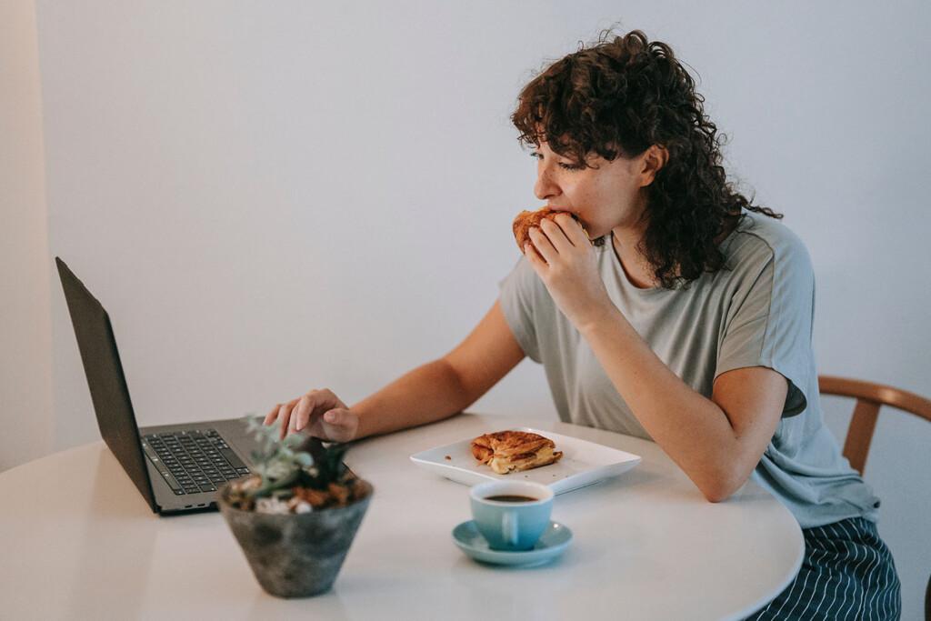 Frau frühstückt vor dem Laptop, um ihre Work-Life-Balance aufrecht zu erhalten. Es gibt andere Wege.