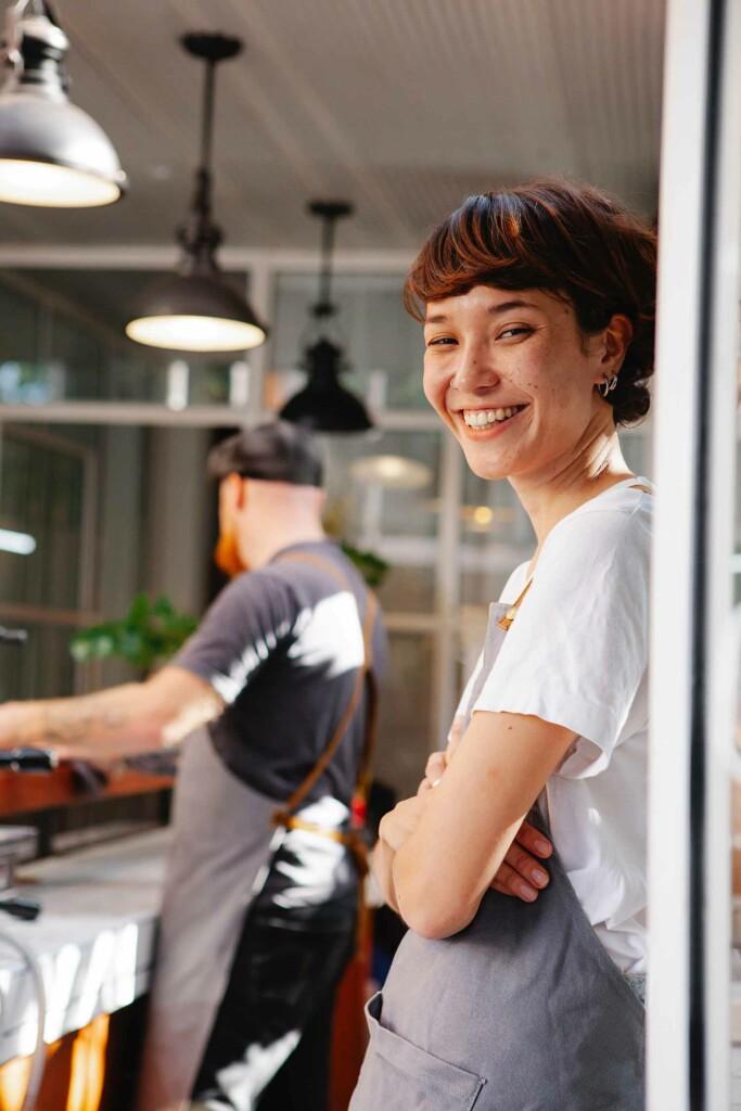 Lachende Frau, die in Café arbeitet, ist auf der Suche nach der passenden Work-Life-Balance