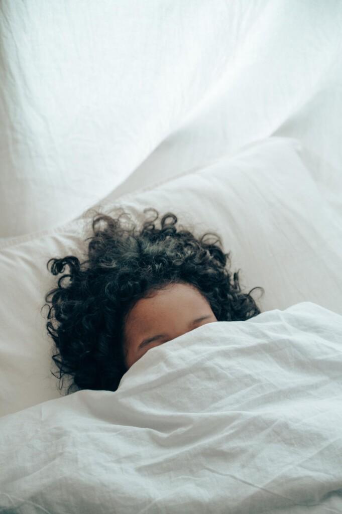 Frau versteckt sich unter der Decke. Als Längschläferin sollte sie ihre Work-Life-Balance an ihren Biorhythmus anpassen