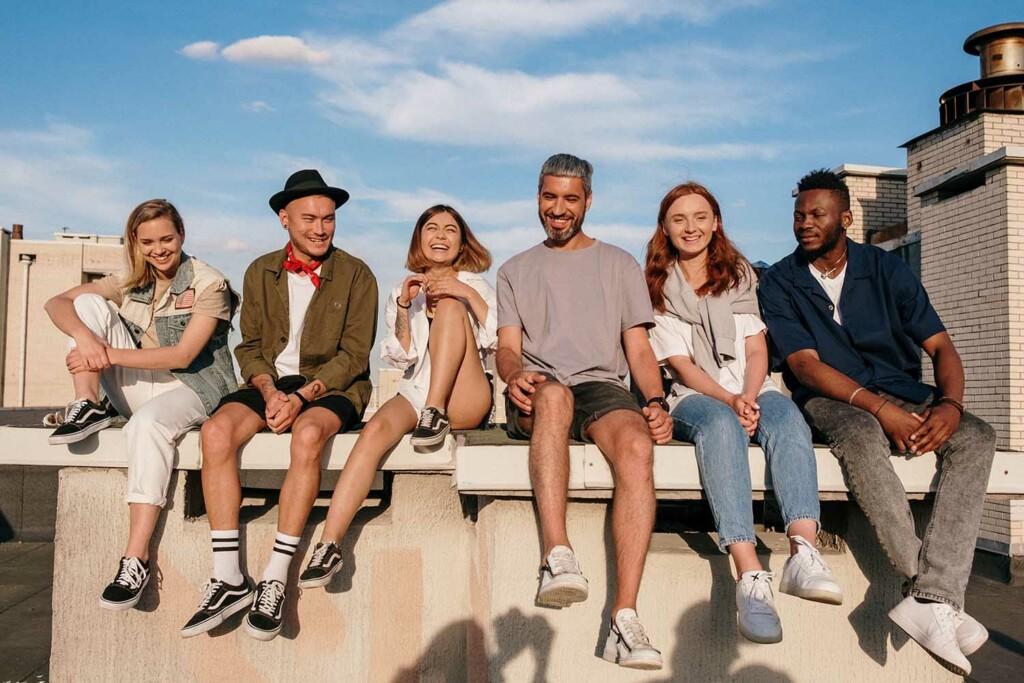 Glückliche junge Mensche sitzen in der Sonne. Sie profitieren von den Möglichkeiten des New Work