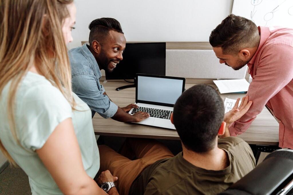 Junge Menschen arbeiten zusammen an einem Laptop, um die Welt zu verändern. Dafür braucht es New Work und das richtige Work-Life-Blending