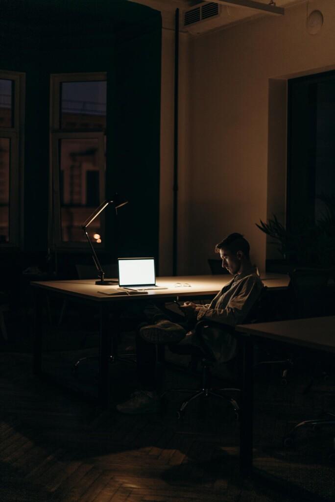 Junger Mann sitzt nachts am Laptop, um zu arbeiten. Ein Beispiel für Work-Life-Blending