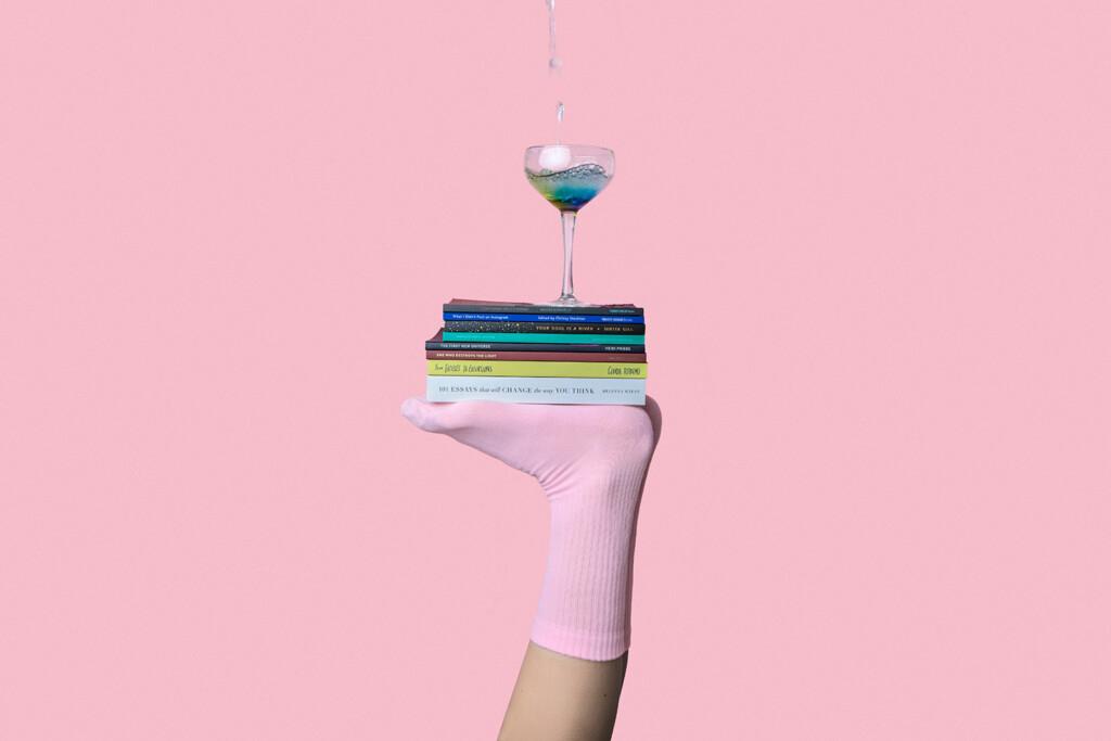 Mensch balanciert Bücher und Glas auf Füßen, um Work-Life-Balance zu symbolisieren