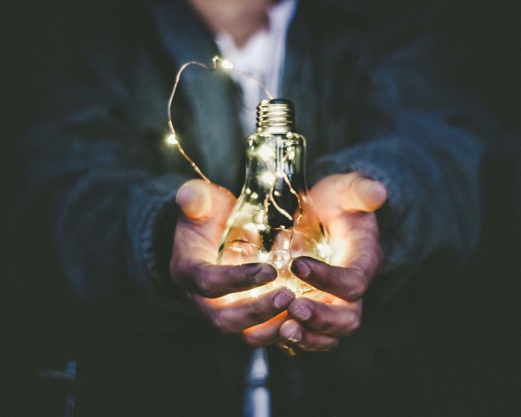 Man hält Glühbirne in der Hand als Zeichen für eine Startup Idee