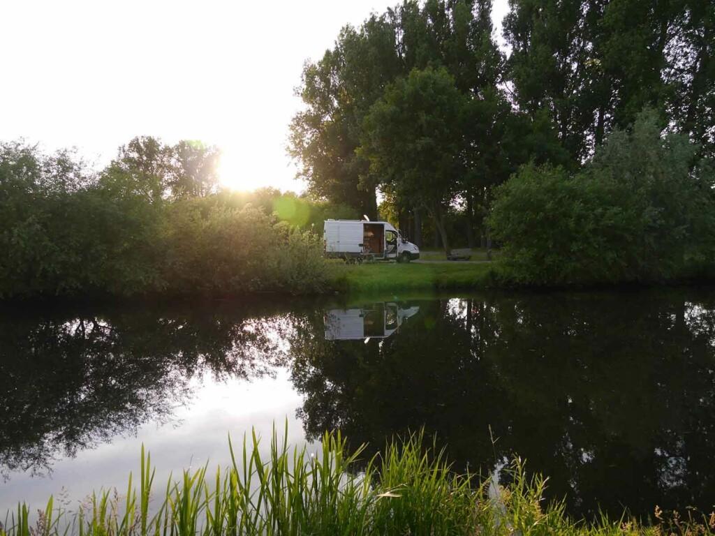 Camper Van steht bei Sonnenuntergang am See