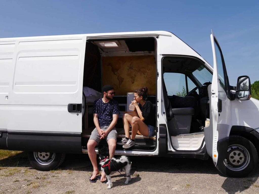 Vanlife Influencer sitzen in ihrem umgebauten Camper