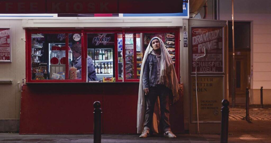 Junger Mann wartet im Regen vor einem Kiosk