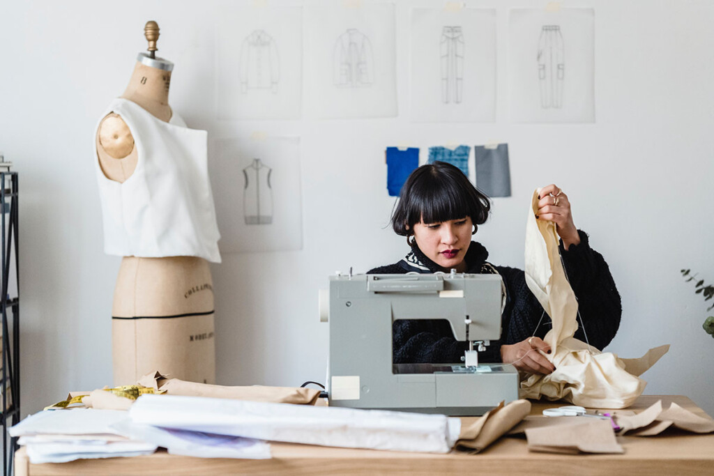 Junge Frau arbeitet als Designerin an der Nähmaschine