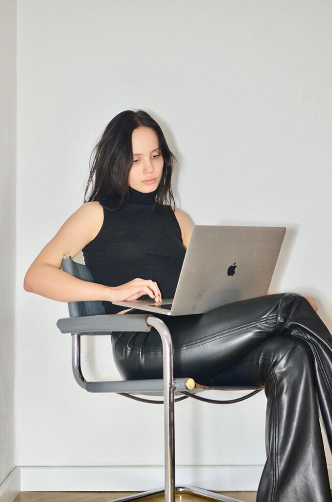 Junge Frau arbeitet sitzend am Macbook