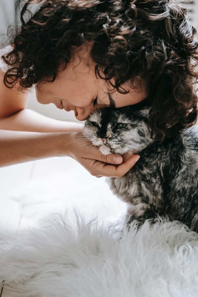 Junge Frau kuschelt Kopf an Kopf mit einer Katze