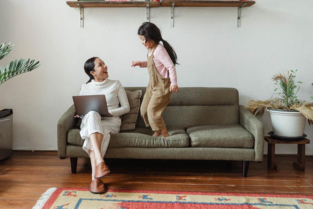 Kleines Mädchen springt neben seiner Mama am Laptop auf und ab