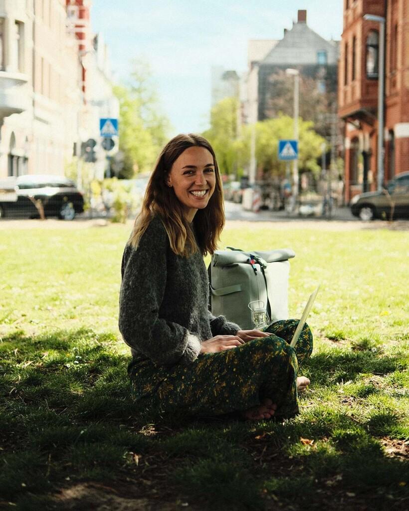 Stella Kocademirci sitzt lachend auf der Wiese