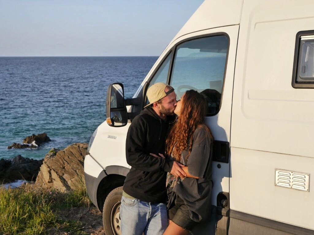 Pärchen Lina und Lennart küsst sich am Meer vor Campervan Giu