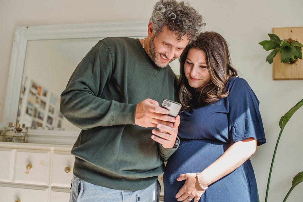 schwangere junge Frau schaut sich auf dem Smartphone Bilder mit ihrem Mann an